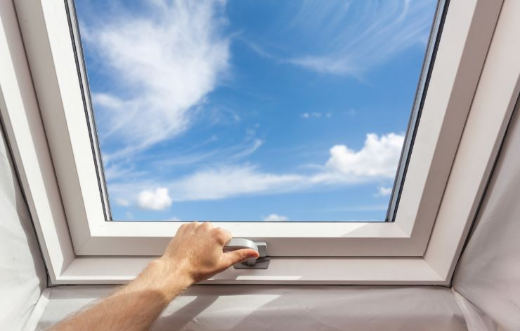 Man opening a skylight looking out to a blue sky | Demers Glass AZ