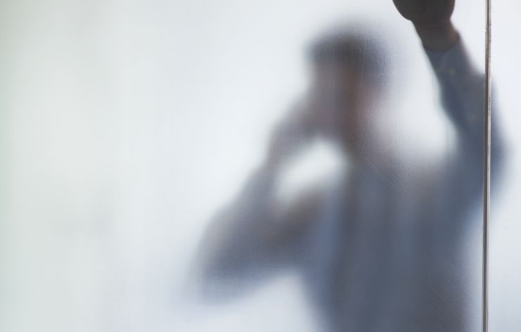 Man on phone behind white out film glass   Demers Glass AZ