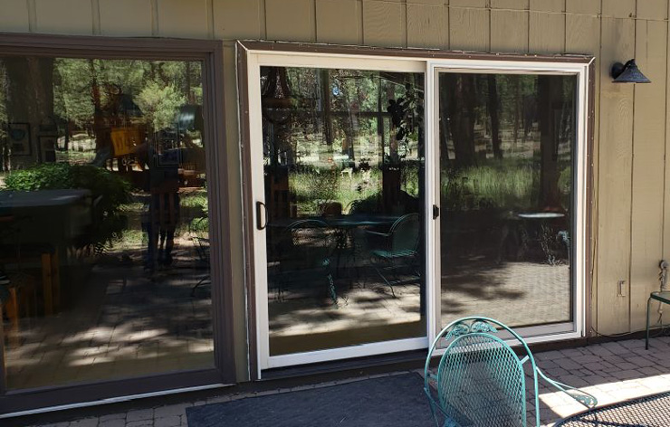 Exterior view of new sliding glass doors leading to a backyard