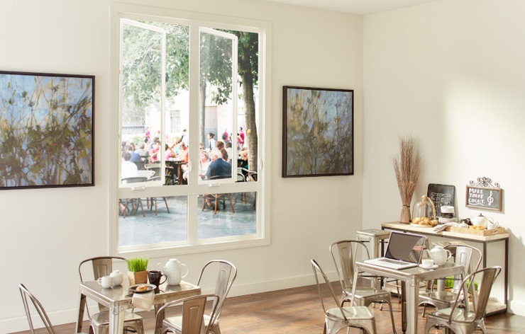 Quaint cafe with small tables and large glass windows by Ply Gem, a Demers Glass partner