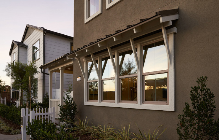 Residential home with modern, white trim windows and wooden awnings by Ply Gem, a Demers Glass Partner