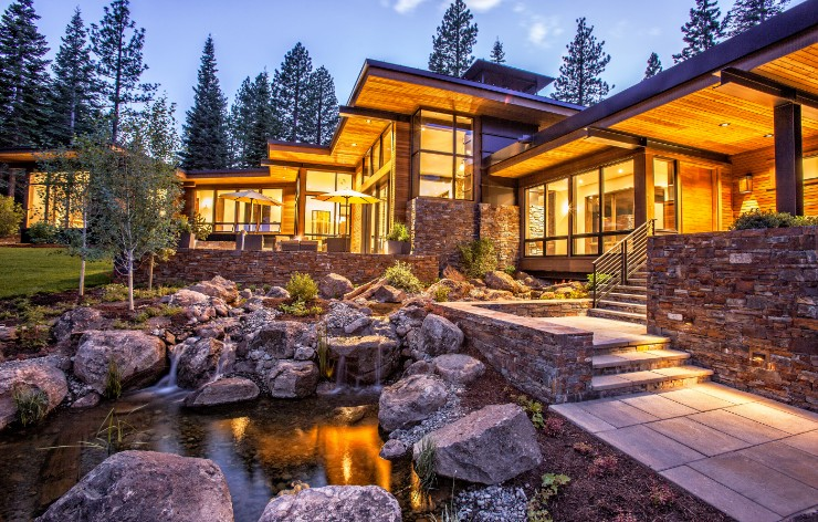 Luxury home exterior at night with large windows by Weather Shield, a Demers Glass partner