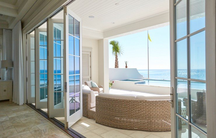 Bi-fold doors opening up to outdoor balcony with an ocean view by Weather Shield, a Demers Glass partner