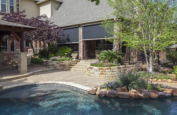 Backyard with a pool and Mirage retractable screens closing off the covered patio