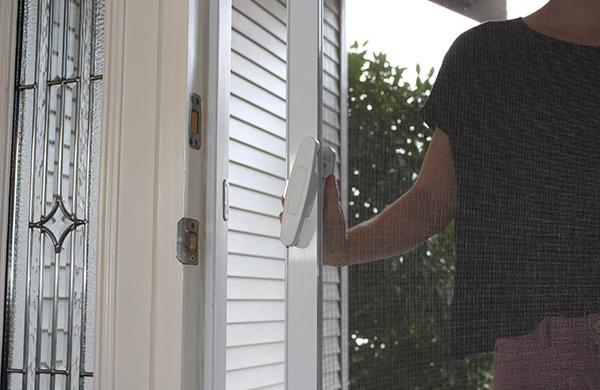 Woman closing Mirage retractable screen door