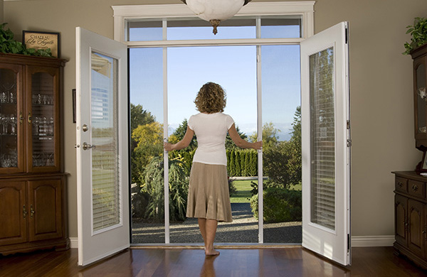 Woman opening up her retractable screen doors in the morning