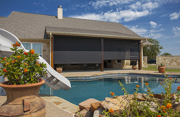 Spacious backyard with a pool and Mirage retractable screens opening up to a covered patio